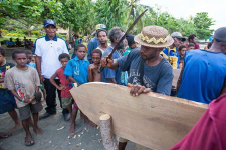A Tupira Surf Club member uses a bush knife to shape his new surfboard. Photo: Robert Weber