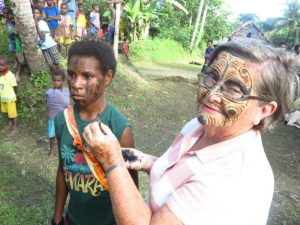 Dame Carol exchanging face painting designs, Tambanum Village